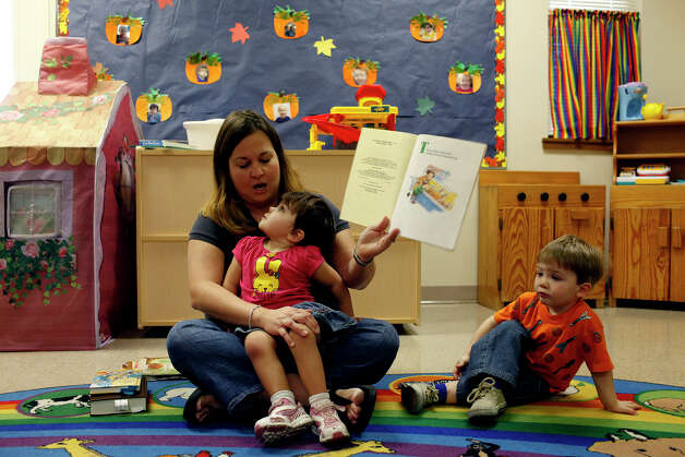 Teacher Heather Beyer reads to Marley Bedford, 3, and Isaac Gold, right, in her pre-school class at First Baptist Church in Fredericksburg on November 8, 2012.b Photo: Lisa Krantz, San Antonio Express-News / © 2012 San Antonio Express-News