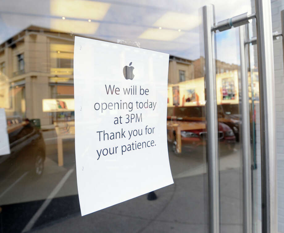 """We will be opening at 3 p.m.,"" reads a sign in the window of the Apple store on Greenwich Avenue, Friday afternoon, March 1, 2013. Heavy rain on Wednesday flooded the basement and caused electrical problems, forcing the store to close this week. Photo: Bob Luckey / Greenwich Time"
