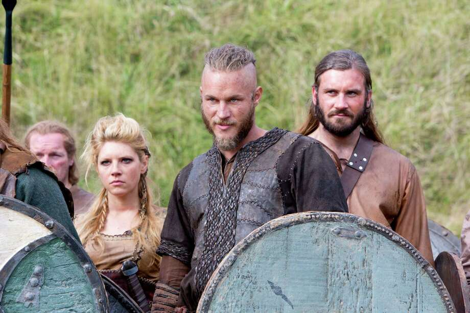 "This image released by History shows Katheryn Winnick, as Lagertha, left, Travis Fimmel, as Ragnar, center, and Clive Standen as Rollo in a scene from ""Vikings,"" premiering Sunday, March 3 on History. (AP Photo/History, Jonathan Hession) Photo: Jonathan Hession"