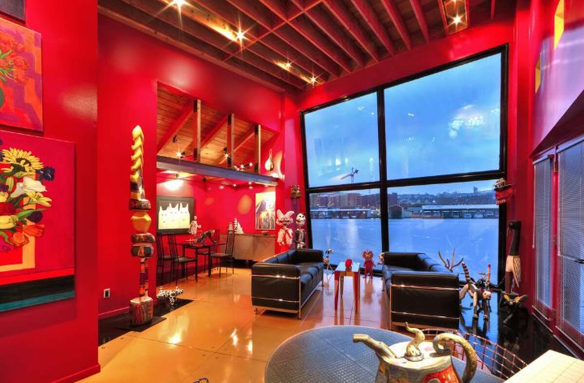 Living room of 3246 Portage Bay Place E. The 1,200-square-foot floating home, built in 2000, has one bedroom, two three-quarter bathrooms, a wall of slanted windows, an eclectic mix of bright wall colors, vaulted, exposed-wood ceilings and built-in shelves, plus a separate 600-square-foot studio and a 1,200-square-foot guest house on a 6,149-square-foot lot. It's listed for $1.598 million.