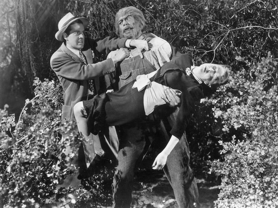 """The Mad MonsterAmerican actor Glenn Strange wearing werewolf makeup, carries a woman in his arms, as another man attempts to restrain him in a scene from director Sam Newfield's film """"The Mad Monster,"""" in 1942. Photo: Hulton Archive, Getty Images / Moviepix"""