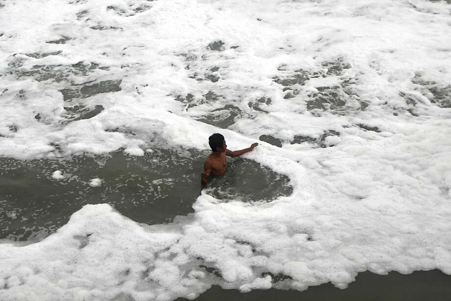 A bracing polar bear swim in an icy river, perhaps?Actually, this fisherman is wading through the suds of sewage-tainted water churned up on a beach in Surabaya, East Java. Eww is right. Photo: Trisnadi, Associated Press