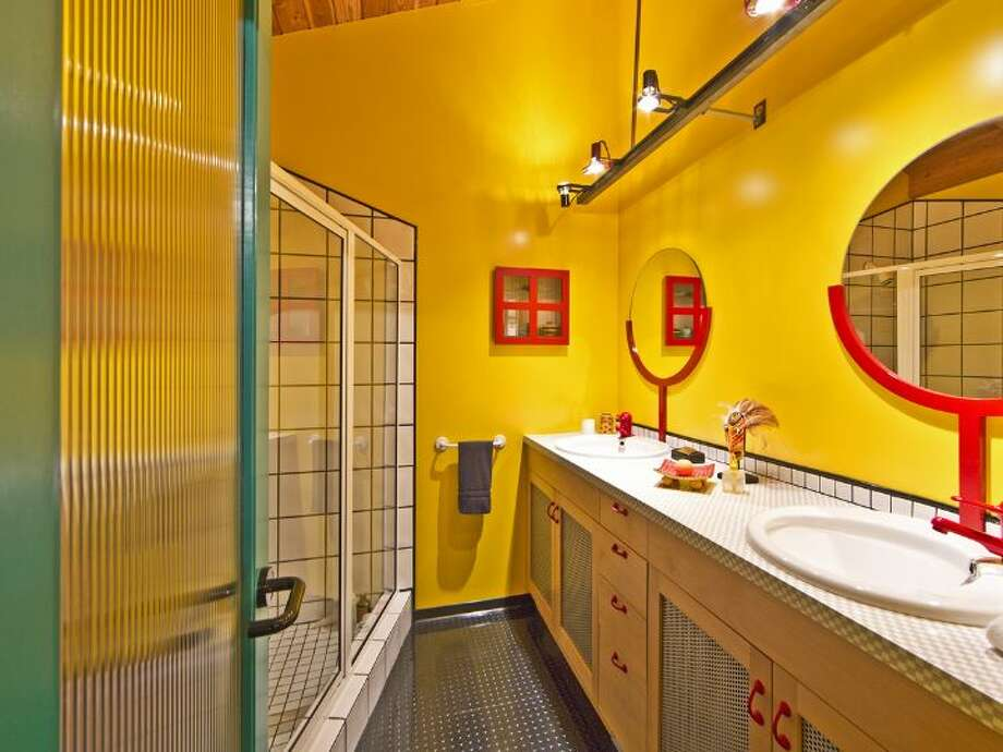 Bathroom of 3246 Portage Bay Place E. The 1,200-square-foot floating home, built in 2000, has one bedroom, two three-quarter bathrooms, a wall of slanted windows, an eclectic mix of bright wall colors, vaulted, exposed-wood ceilings and built-in shelves, plus a separate 600-square-foot studio and a 1,200-square-foot guest house on a 6,149-square-foot lot. It's listed for $1.598 million. Photo: Courtesy Tere And David Foster/Windermere Real Estate