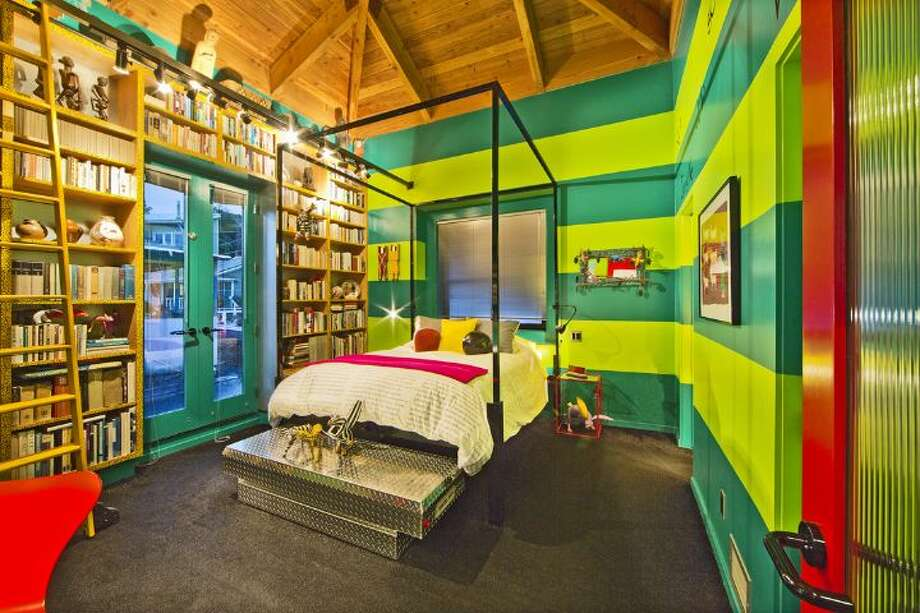 Bedroom of 3246 Portage Bay Place E. The 1,200-square-foot floating home, built in 2000, has one bedroom, two three-quarter bathrooms, a wall of slanted windows, an eclectic mix of bright wall colors, vaulted, exposed-wood ceilings and built-in shelves, plus a separate 600-square-foot studio and a 1,200-square-foot guest house on a 6,149-square-foot lot. It's listed for $1.598 million. Photo: Courtesy Tere And David Foster/Windermere Real Estate
