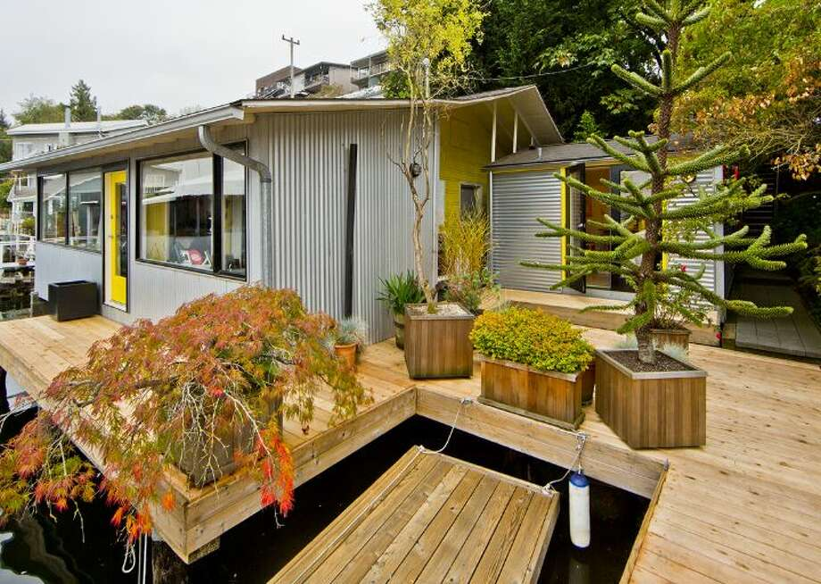 Exterior of 3246 Portage Bay Place E. The 1,200-square-foot floating home, built in 2000, has one bedroom, two three-quarter bathrooms, a wall of slanted windows, an eclectic mix of bright wall colors, vaulted, exposed-wood ceilings and built-in shelves, plus a separate 600-square-foot studio and a 1,200-square-foot guest house on a 6,149-square-foot lot. It's listed for $1.598 million. Photo: Courtesy Tere And David Foster/Windermere Real Estate