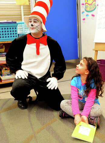 Second grade student Kaylie Batista looks up at Sam Pollastro, dressed as The Cat in the Hat, during his visit to her classroom at Bradley Elementary School in Derby, Conn. Friday, Mar. 1, 2013 in honor of Dr. Seuss' birthday. The children's author was born March 2, 1904. Photo: Autumn Driscoll / Connecticut Post