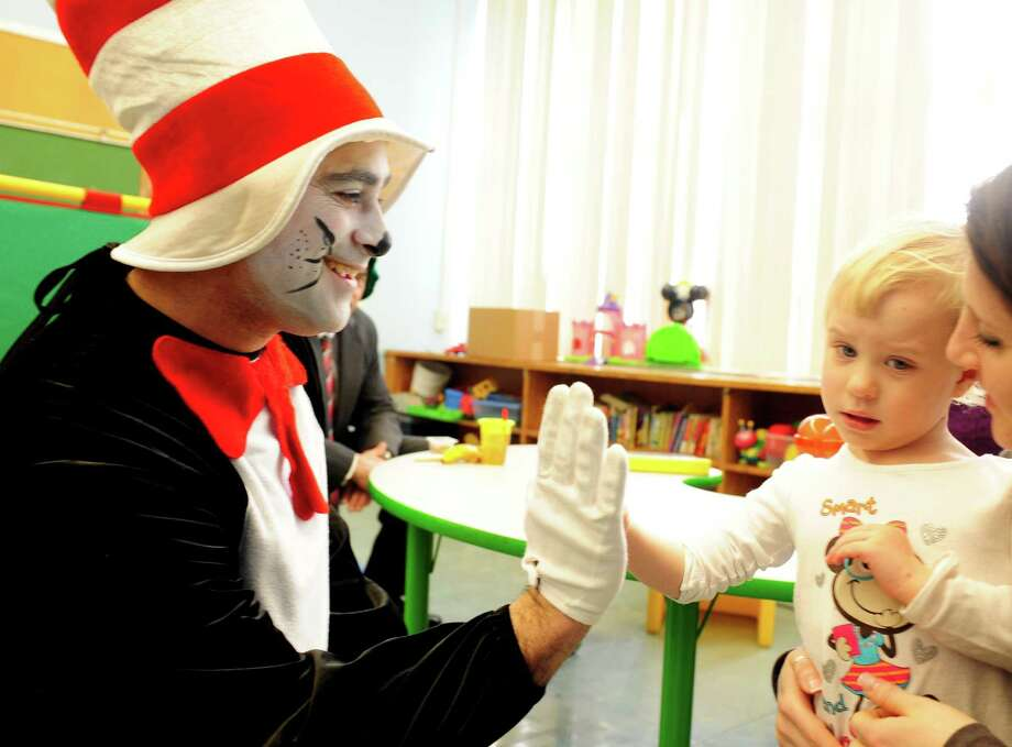 Sam Pollastro, dressed as The Cat in the Hat, gets a high-five from four-year-old Chloe Richards Friday, Mar. 1, 2013 during his visit to Bradley Elementary School in Derby, Conn. in honor of the children's author's birthday. Dr. Seuss was born March 2, 1904. Photo: Autumn Driscoll / Connecticut Post