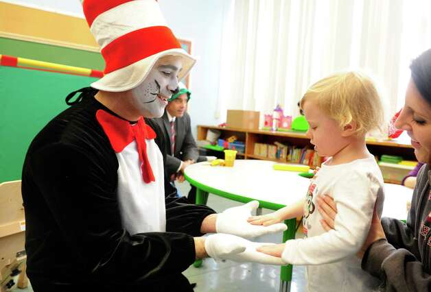 Sam Pollastro, dressed as The Cat in the Hat, gets a greeting from four-year-old Chloe Richards Friday, Mar. 1, 2013 during his visit to Bradley Elementary School in Derby, Conn. in honor of the children's author's birthday. Dr. Seuss was born March 2, 1904. Photo: Autumn Driscoll / Connecticut Post