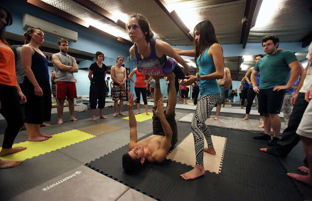 Ruthie Ocean is balanced by Mark Stewart as he teaches a class in AcroYoga at District 24 on February 21, 2013. Sarah Septien serves as spotter in the exercise. Photo: TOM REEL, San Antonio Express-News / San Antonio Express-News