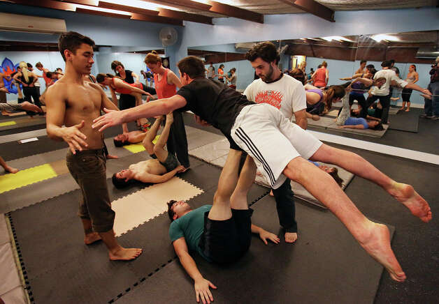 Mark Stewart (left) gets Colin Standifird balanced as Matthew Greene holds him with his legs during a class in AcroYoga at District 24 on February 21, 2013. The exercise requires a spotter, Eric Bittle in this group. Photo: TOM REEL, San Antonio Express-News / San Antonio Express-News