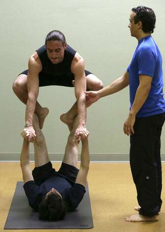 Acrobatics coach Vladimir Vladev, right, spots for Mark Bennett, above, as he is supported by Alejandro Reyes. Tuesday, Feb. 26, 2013. Photo: Bob Owen, San Antonio Express-News / © 2012 San Antonio Express-News