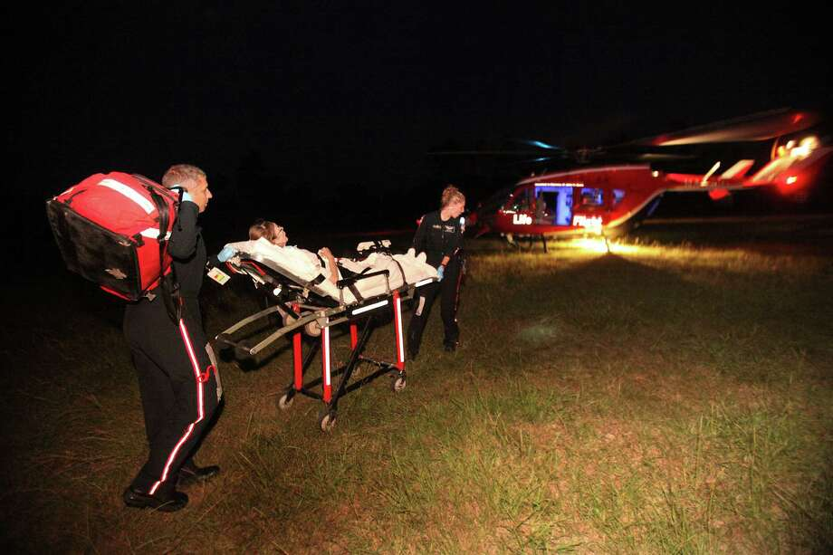 Aaron Young, 39, Life Flight Paramedic, and Amanda Leight, 29, Flight Life Nurse, transports a critical patient from Liberty County to MD Anderson via Life Flight Memorial Hermann on Thursday, Aug. 18, 2011, in Houston.    ( Mayra Beltran / Chronicle ) Photo: Mayra Beltran, Staff / © 2011 Houston Chronicle