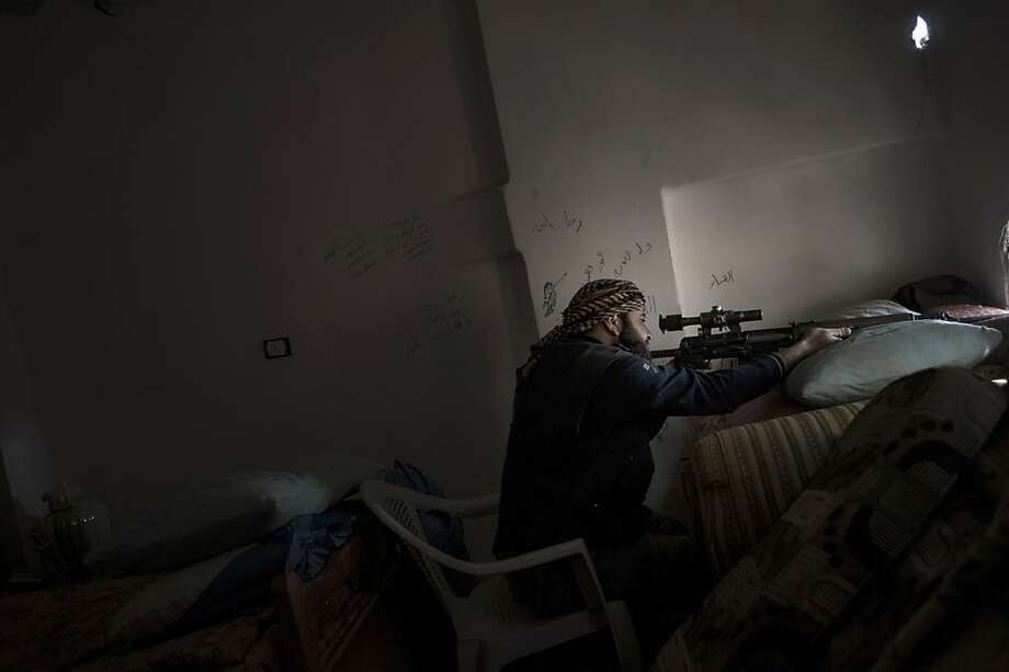 A Rebel sniper takes aim at government forces with his Dragunov SVD rifle from a house in the Syrian eastern city of Deir Ezzor, on February 28, 2013. The United States said it would for the first time provide direct aid to Syrian rebels, but not the arms they had hoped for, as well as $60 million in extra assistance to the political opposition. Photo: Zac Baillie, AFP/Getty Images