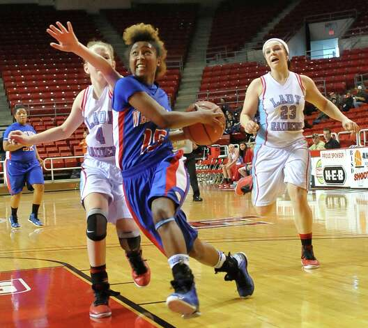 Lady Bruin, #15, Kiera Mickens goes for two points right past Lady Raider defender #4, Hannah Holt, left, and #23, Taylor Holt. The Lumberton Lady Raiders and the West Brook Lady Bruins met on the court Thursday morning November 29, 2012 in a first round basketball game in the annual YMBL Basketball Tournament. The Bruins won 54-41.  Dave Ryan/The Enterprise Photo: Dave Ryan