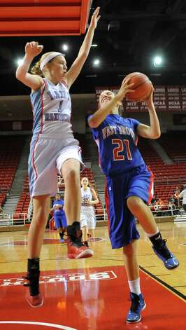 Lady Bruin, #21, Danielle Metoye, right, goes up for the shot as Lady Raider #1, Megan Worry, left, tries for the block. The Lumberton Lady Raiders and the West Brook Lady Bruins met on the court Thursday morning November 29, 2012 in a first round basketball game in the annual YMBL Basketball Tournament. The Bruins won 54-41.  Dave Ryan/The Enterprise Photo: Dave Ryan