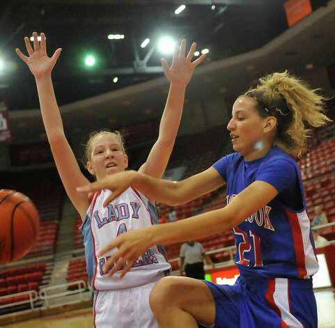 Lady Bruin, #21, Danielle Metoye, right, gets a pass around Lady Raider #4, Hannah Holt. The Lumberton Lady Raiders and the West Brook Lady Bruins met on the court Thursday morning November 29, 2012 in a first round basketball game in the annual YMBL Basketball Tournament. The Bruins won 54-41.  Dave Ryan/The Enterprise Photo: Dave Ryan