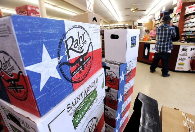 A customer checks out near a stack of Texas beer at Sam's Package in Beaumont.  Photo taken Thursday, February 21, 2013 Guiseppe Barranco/The Enterprise Photo: Guiseppe Barranco, STAFF PHOTOGRAPHER / The Beaumont Enterprise