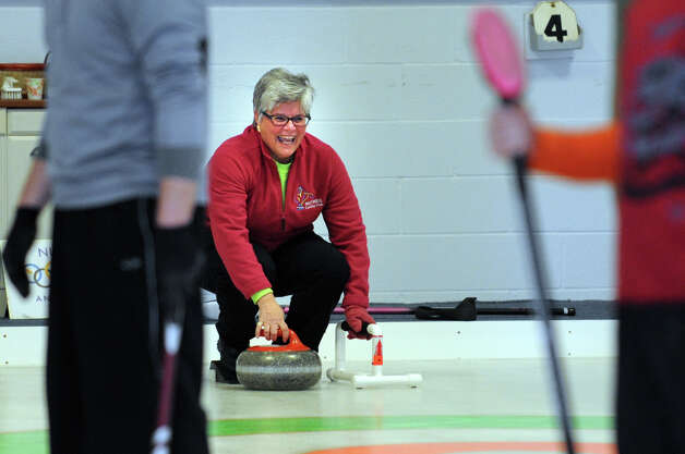 Jayne Beattie, of Norwalk, gets ready to deliver a curling stone during a tournament game Tuesday, Feb. 26, 2013 at the Nutmeg Curling Club in Bridgeport, Conn. Photo: Autumn Driscoll / Connecticut Post
