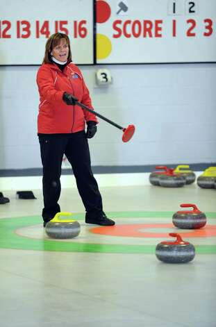 Naida Leslie, of New Canaan, directs her teammates as they sweep a curling stone during a tournament game Tuesday, Feb. 26, 2013 at the Nutmeg Curling Club in Bridgeport, Conn. Photo: Autumn Driscoll / Connecticut Post