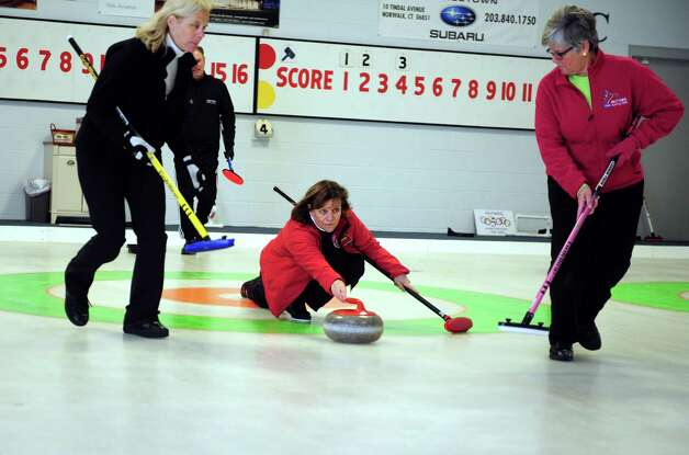 Naida Leslie, of New Canaan, releases a curling stone during a tournament game Tuesday, Feb. 26, 2013 at the Nutmeg Curling Club in Bridgeport, Conn.  Teammates Kathy Morley, of New Canaan, left, and Jayne Beattie, of Norwalk, get ready to sweep the ice in front of the stone as needed. Photo: Autumn Driscoll / Connecticut Post