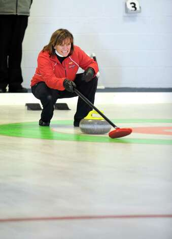 Naida Leslie, of New Canaan, watches a curling stone's direction during a tournament game Tuesday, Feb. 26, 2013 at the Nutmeg Curling Club in Bridgeport, Conn. Photo: Autumn Driscoll / Connecticut Post