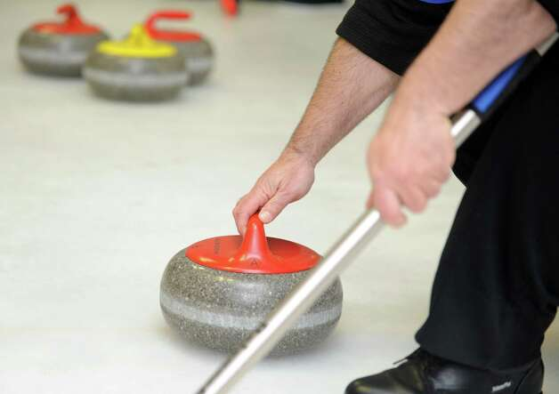 A player gets ready to deliver a curling stone during a tournament game Tuesday, Feb. 26, 2013 at the Nutmeg Curling Club in Bridgeport, Conn. Photo: Autumn Driscoll / Connecticut Post