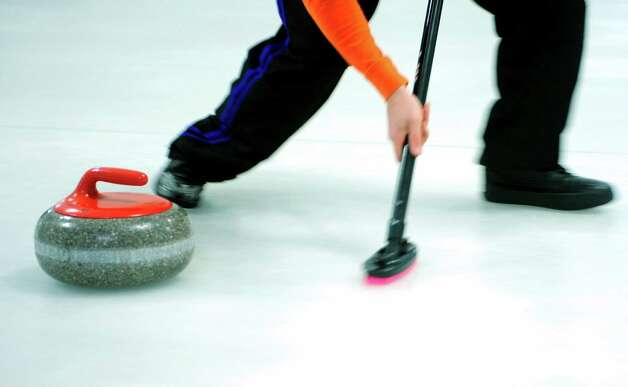 A player sweeps a curling stone during a tournament game Tuesday, Feb. 26, 2013 at the Nutmeg Curling Club in Bridgeport, Conn. Photo: Autumn Driscoll / Connecticut Post