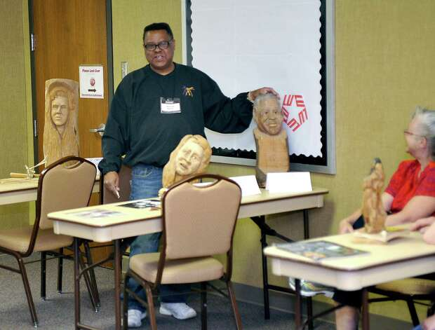 Herman Davis, left, a local woodcarver and story teller, was at the Beaumont Public Library Downtown branch this week, demonstrating his art of carving all types of wood, and telling his folk stories during a program for adults. He brought with him several large examples of carvings that he has finished as well as continues to carve on.   Dave Ryan/The Enterprise