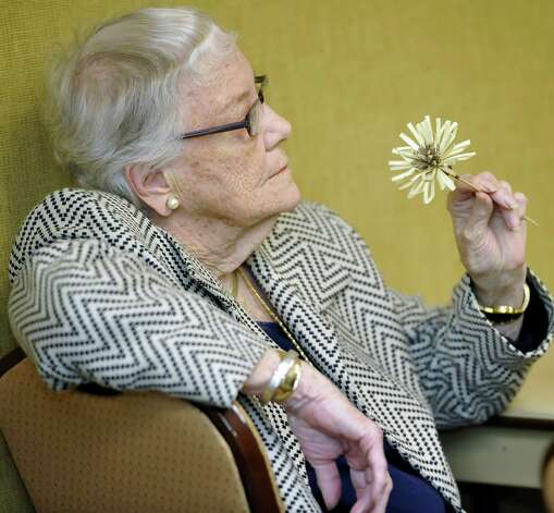 One of the guests, Nan Williams, holds one of Herman's hand made paper flowers that he had given her after making is as part of his demonstration. Herman Davis, a local woodcarver and story teller, was at the Beaumont Public Library Downtown branch this week, demonstrating his art of carving all types of wood, and telling his folk stories during a program for adults. He showed examples of how he carves flowers, birds, and even roosters with a sharp blade and a stick of wood. He is hardly ever without them, even when he is just talking.    Dave Ryan/The Enterprise