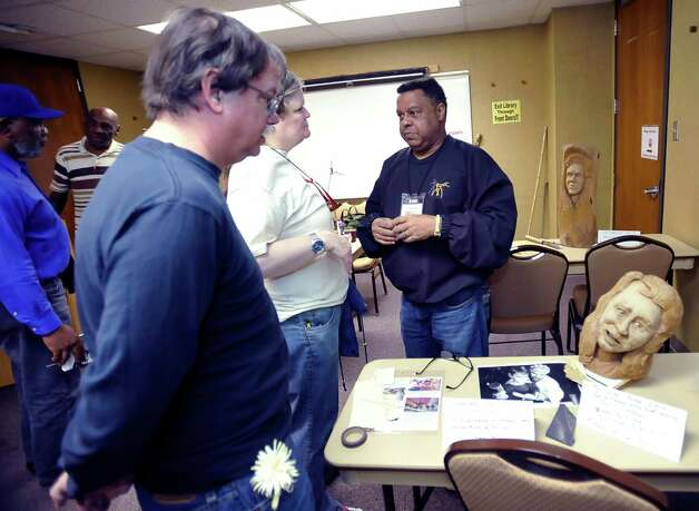 Herman Davis, right, a local woodcarver and story teller, was at the Beaumont Public Library Downtown branch this week, demonstrating his art of carving all types of wood, and telling his folk stories during a program for adults. He spent time afterwards answering questions one-on-one with his guests. In the background are several large examples of carving that he has finished as well as continues to carve on.   Dave Ryan/The Enterprise
