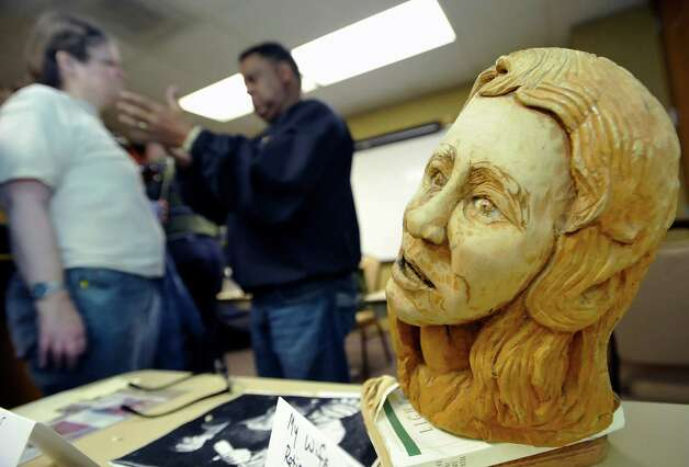 This finished bust is of his wife, also mounted on a book first, then a wooden base. Herman Davis, center, a local woodcarver and story teller, was at the Beaumont Public Library Downtown branch this week, demonstrating his art of carving all types of wood, and telling his folk stories during a program for adults. He brought with him several large examples of carving that he has finished as well as continues to carve on.   Dave Ryan/The Enterprise