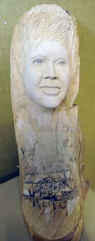 This in progress bust is of Beaumont MAyor Becky Ames that he carved into a log.  But because she has changed her hair style, he still has work to do on it. Herman Davis, a local woodcarver and story teller, was at the Beaumont Public Library Downtown branch this week, demonstrating his art of carving all types of wood, and telling his folk stories during a program for adults. He brought with him several large examples of carving that he has finished as well as continues to carve on.   Dave Ryan/The Enterprise