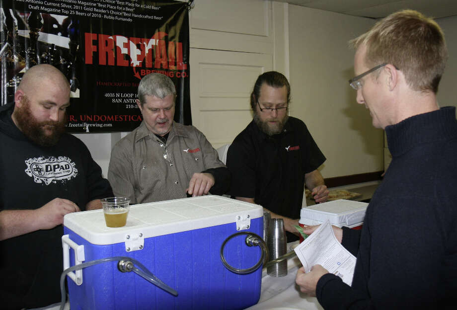 Branchline Brewing Company's Les Locke and Freetail's Gary Butler and Jason Davis pour samples of Freetail beers for attendees at Texas Public Radio's Views and Brews session covering pending Texas beer law legislation.