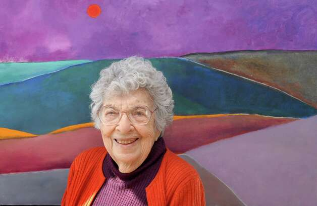 "Henriette Simon Picker sits in front of a paining done in 1989 called ""Landscape"" at the PMW Gallery in Stamford, Conn. on Monday February 25, 2013. A retrospective show of her work will open at the gallery on March 3 and runs until April 14. Photo: Dru Nadler / Stamford Advocate Freelance"