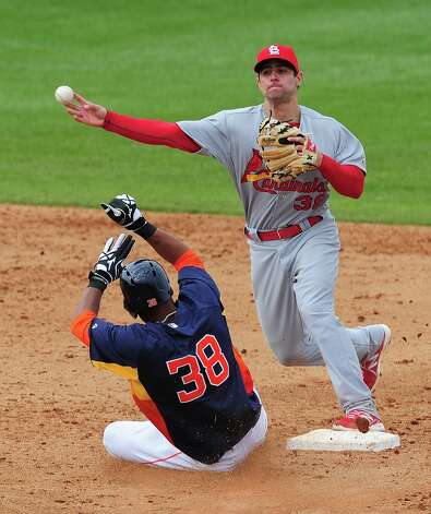 Pete Kozma turns a double play as Jimmy Paredes slides into second base. Photo: Scott Cunningham / 2013 Getty Images