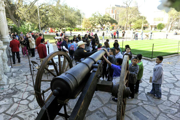 Children look over a replica of the 18 pound cannon fired in response to General Santa Anna's demand for surrender at the Alamo Friday. The Daughters of the Republic of Texas will markTexas Independence Day today with various events at the Alamo. The events include live demonstrations, living history and history talks. Photo: Robin Jerstad