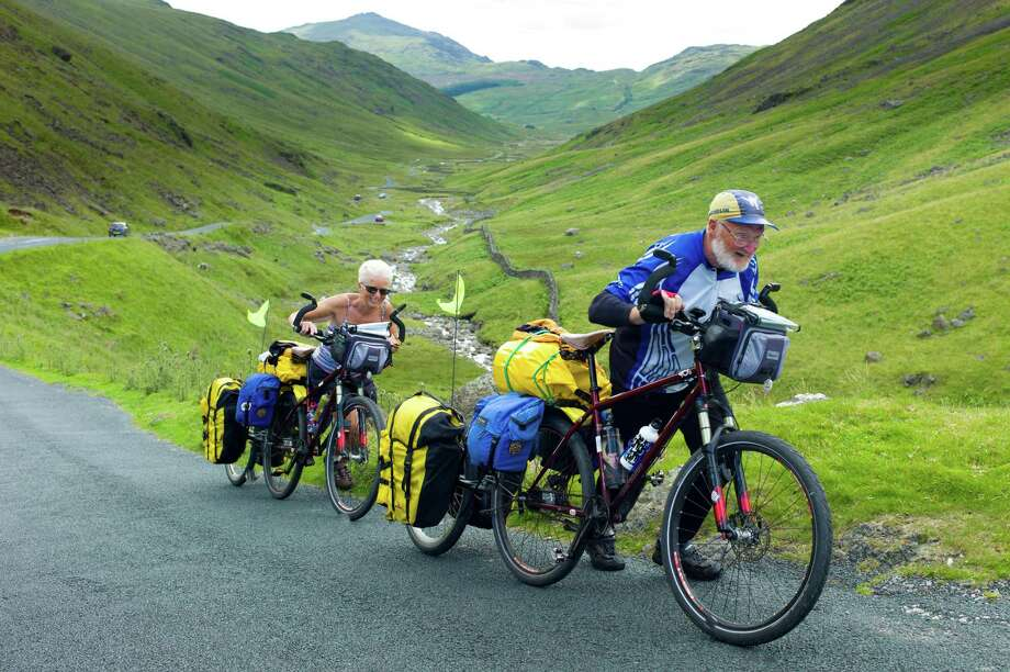 Cyclists on roadway through Wrynose Pass in the Dudden Valley part of the Lake District National Park, Cumbria, UK Photo: Tim Graham / Tim Graham