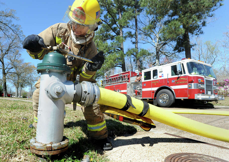 Largely in part to an efficient system of transporting water to a fire, Beaumont residents can soon expect a decrease in their insurance bill. Dan Howell disconnects a hose from a hydrant after extinguishing a fire in Beaumont on Friday. No injuries were reported from the fire. Photo taken Friday, March 01, 2013 Guiseppe Barranco/The Enterprise Photo: Guiseppe Barranco, STAFF PHOTOGRAPHER / The Beaumont Enterprise