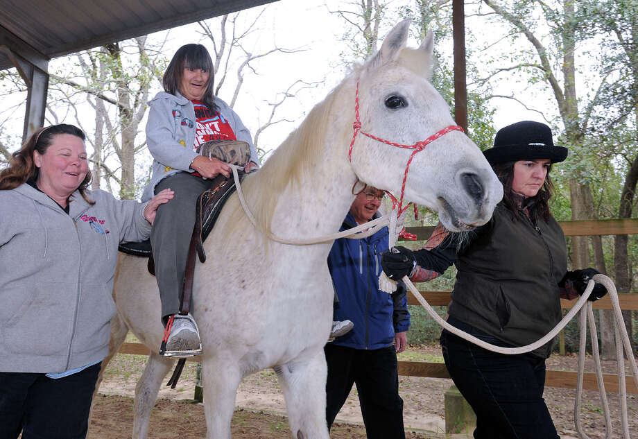 Wheelchair bound from a stroke, Paula Erickson, 60, is escorted while riding a horse at Spirit Stable in Rose City Thursday. As part of a new program at the Oaks at Beaumont, each month a guest will participate in an event of their choosing. Erickson, who chose horseback riding, is the first.  Photo taken Thursday, February 28, 2013 Guiseppe Barranco/The Enterprise Photo: Guiseppe Barranco, STAFF PHOTOGRAPHER / The Beaumont Enterprise