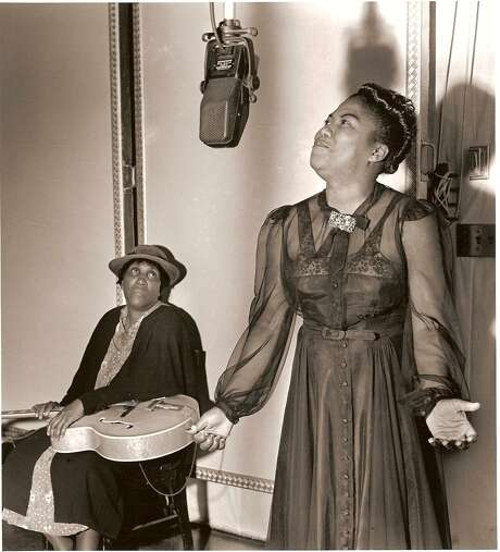 """Sister Rosetta Tharpe sings while her mother, Katie Bell, left, holds her daughter's guitar. """"Sister Rosetta Tharpe: The Godmother of Rock & Roll"""" was featured on PBS recently. Photo: Charles Peterson / Courtesy Of PBS American Masters"""