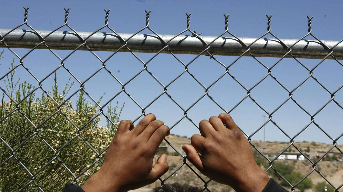 The hands of an immigrant returned to Mexico from the U.S. grasp the chain-link fence on the border at Nogales, Mexico.
