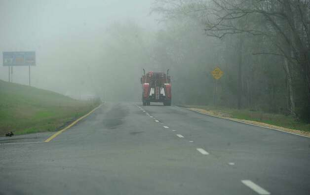 On Monday morning February 25, 2013,  Beaumont was blanketed in fog, causing everything, not on the ground per se, to be viewed in shades of gray.  I got the idea coming to work to just drive around and shoot scenes at random.  This is  Neff Brothers tow truck heading down the service road east bound.  The road looks like it just disappears into the trees.  Dave Ryan/The Enterprise