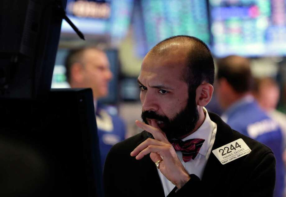 This Thursday, Feb. 28, 2013, photo shows specialist Fabian Caceres works at his post on the floor of the New York Stock Exchange. The stock market pushed higher Thursday afternoon, sending the Dow tantalizingly close to a record high. (AP Photo/Richard Drew) Photo: Richard Drew