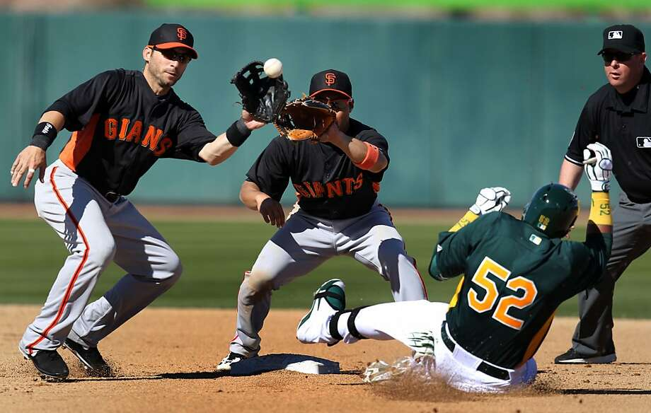 Giants' Marco Scutaro (left) has the inside track on taking a throw and trying to tag Yoenis Céspedes. Photo: Lance Iversen, The Chronicle