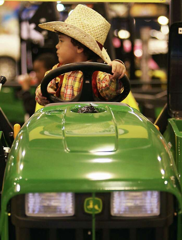 Three-year-old Justin Garcia sits on a John Deere 3032E tractor at the Shoppa's Farm Supply booth during the Houston Livestock Show and Rodeo in Reliant Park Tuesday, Feb. 26, 2013, in Houston. ( James Nielsen / Houston Chronicle ) Photo: James Nielsen, Staff / © 2013  Houston Chronicle