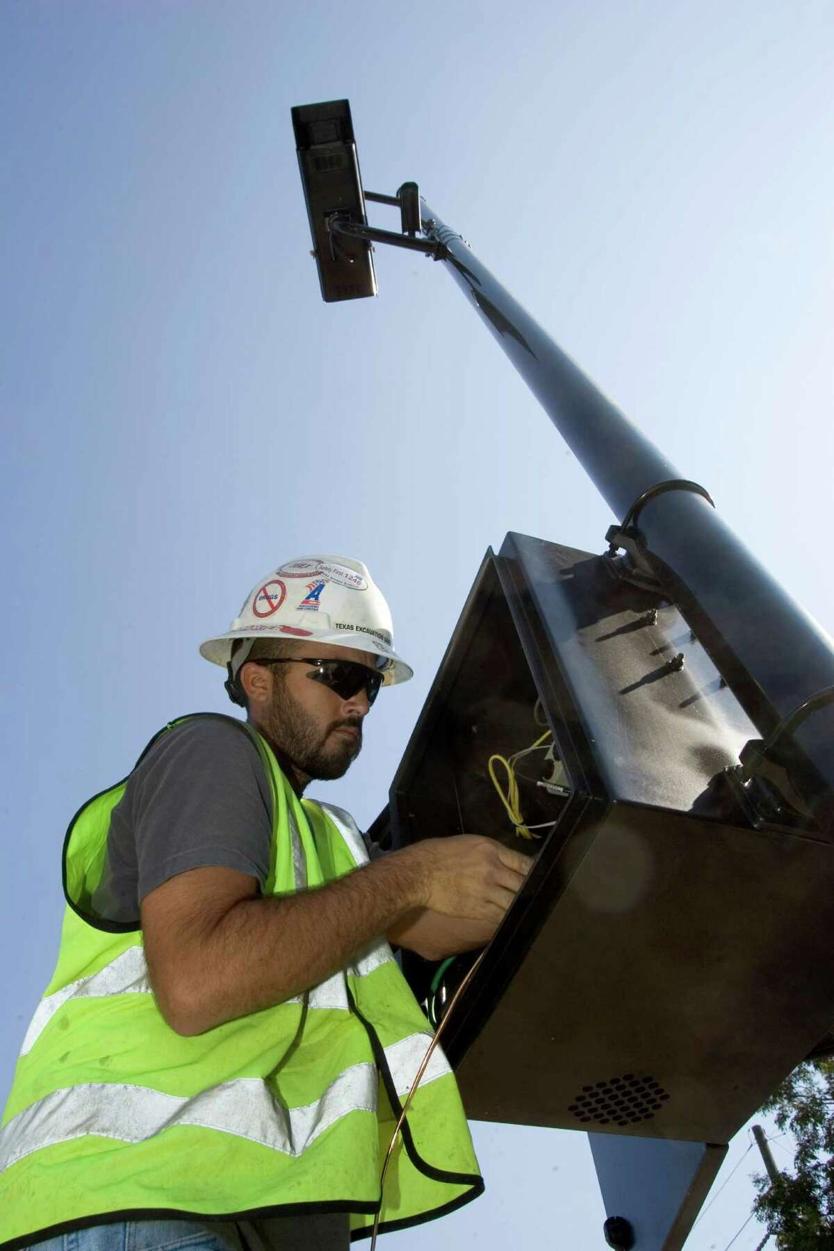 Danny Gibbs works on the wiring in a red light camera at the intersection of Texas 6 and Lexington in 2007 in Sugar Land. (Brett Coomer/Chronicle )
