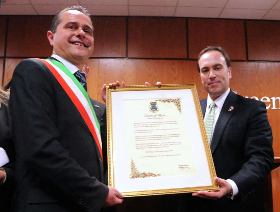 "At left, Mayor Stefano Leone of Rose in Calabria, Italy, presents a proclamation to Greenwich First Selectman Peter Tesei during the âÄúFrom Italy To America âÄù ceremony designating two towns in southern Italy, Morra De Sanctis in Campania and Rose, as sister cities of Greenwich, at Greenwich Town Hall, Friday night, March 1, 2013. Tesei traces his roots to Rose. Many of GreenwichâÄôs Italian-American residents emigrated from these two areas of Italy. Following the ceremony, the guests and Greenwich Historical Society members attended the opening of ""From Italy to America"" at the Greenwich Historical Society's Storehouse Gallery. The exhibition, which opens to the public Saturday, features a range of archival photographs, documents and objects dating from the 1880s that relate to the immigrant experience. Many of the items were collected during the Society's ""Discovery Days, "" which were held this past September through December. More than 100 people brought in objects for the exhibition that illustrate the experiences, traditions, challenges and contributions of Italian immigrants in Greenwich. Photo: Bob Luckey / Greenwich Time"