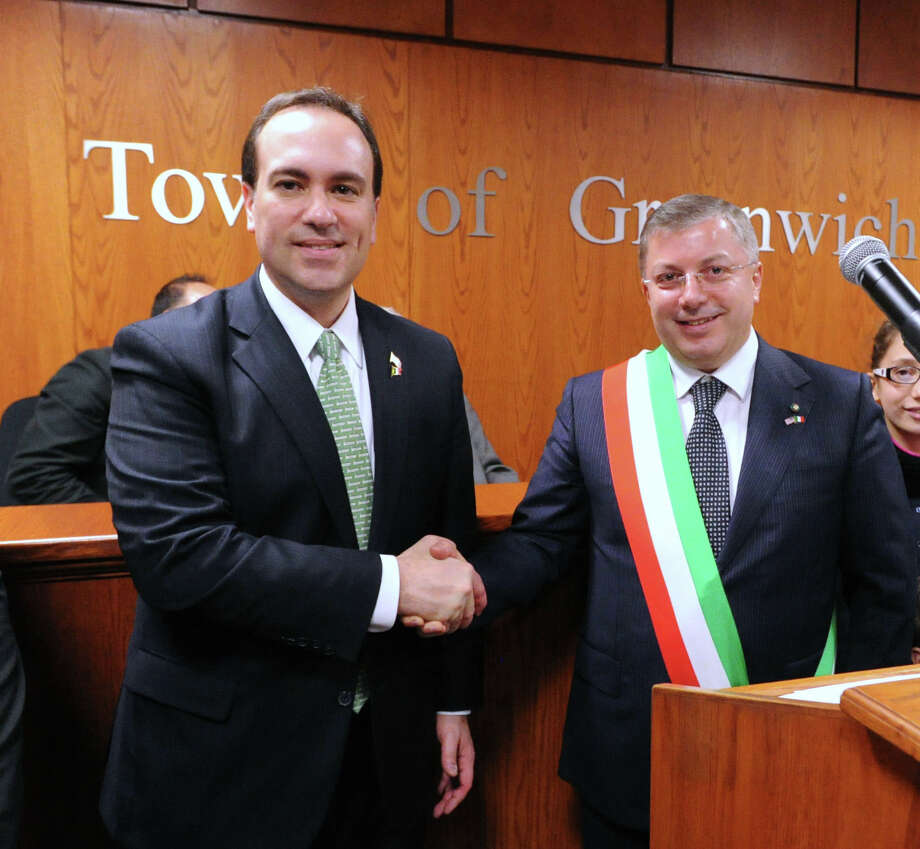 "At left, Greenwich First Selectman Peter Tesei shakes hands with Mayor Gerardo Capozza of Morra De Sanctis in Campania, Italy, during the âÄúFrom Italy To America âÄù ceremony designating two towns in southern Italy, Morra De Sanctis and Rose in Calabria, as sister cities of Greenwich, at Greenwich Town Hall, Friday night, March 1, 2013.  Many of GreenwichâÄôs Italian-American residents emigrated from these two areas of Italy. Following the ceremony, the guests and Greenwich Historical Society members attended the opening of ""From Italy to America"" at the Greenwich Historical Society's Storehouse Gallery. The exhibition, which opens to the public Saturday, features a range of archival photographs, documents and objects dating from the 1880s that relate to the immigrant experience. Many of the items were collected during the Society's ""Discovery Days, "" which were held this past September through December. More than 100 people brought in objects for the exhibition that illustrate the experiences, traditions, challenges and contributions of Italian immigrants in Greenwich. Photo: Bob Luckey / Greenwich Time"