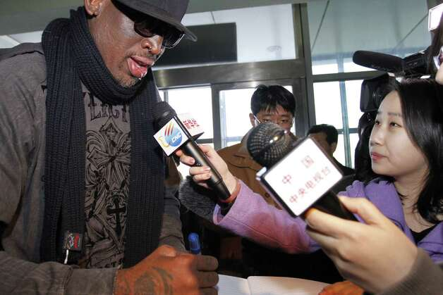 Former NBA star Dennis Rodman, left, speaks to the media at the airport in Pyongyang, before he leaves North Korea Friday, March 1, 2013.   Rodman hung out with North Korea's Kim Jong Un during his improbable journey to Pyongyang, watching the Harlem Globetrotters with the leader and later drinking and dining on sushi with him.(AP Photo/Kim Kwang Hyon) Photo: Kim Kwang Hyon