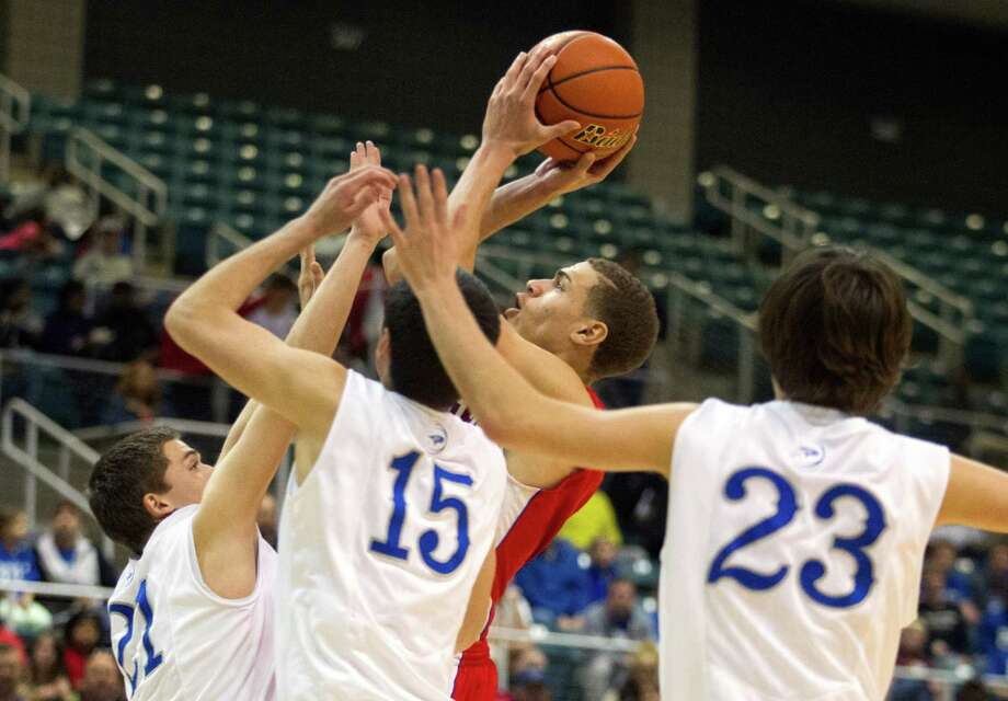 Brazosport guard Khory Ross (1) shoots over Georgetown forwards Brad Huntsman (21), Mitchell Smith (15), and guard Sam Talbert during the fourth quarter of the 4A Region III tournament at the Merrell Center on Friday, March 1, 2013, in Katy. Photo: J. Patric Schneider, For The Chronicle / © 2013 Houston Chronicle